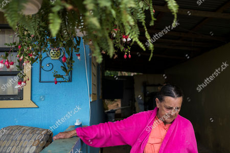 Marta Bermudez Robles stands outside her home that is still without electricity since Hurricane Irma and Maria in Adjuntas, Puerto Rico. Returning power to residents in hard to reach areas is slow work, and it has stretched nearly two months past the date when officials had promised that everyone in Puerto Rico would be energized