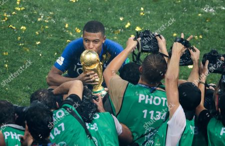 Kylian Mbappe poses for photographers with the World Cup Trophy
