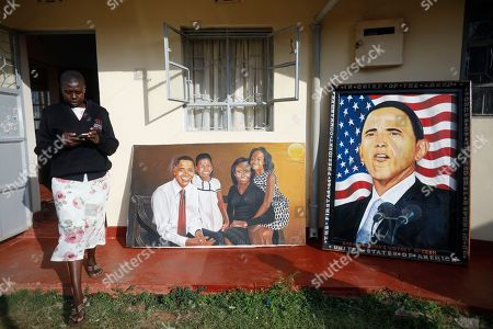 A woman walks in front of paintings depicting former US president Barack Obama and his family prior to an opening ceremony of the Sauti Kuu Sports, Vocational and Training Centre in his ancestral home Kogelo, some 400km west of the capital Nairobi, Kenya, 16 July 2018. Barack Obama visited his ancestral home in western Kenya to attend the opening ceremony of the centre founded by his half-sister Auma Obama, after having met with Kenyan President Uhuru Kenyatta and opposition politician Raila Odinga in Nairobi the previous day. After Kenya, Obama is scheduled to travel to South Africa where he will deliver the annual Nelson Mandela lecture in Johannesuburg.