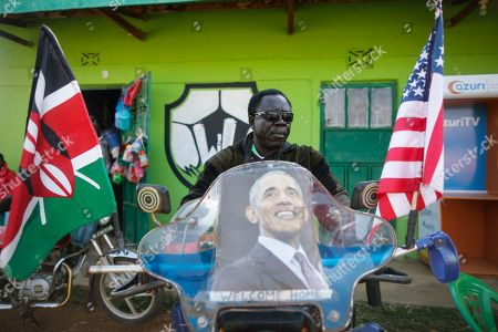 A supporter of former US president Barack Obama sits on his motorcycle decorated with Obama's portrait, prior to an opening ceremony of the Sauti Kuu Sports, Vocational and Training Centre in his ancestral home Kogelo, some 400km west of the capital Nairobi, Kenya, 16 July 2018. Barack Obama visited his ancestral home in western Kenya to attend the opening ceremony of the centre founded by his half-sister Auma Obama, after having met with Kenyan President Uhuru Kenyatta and opposition politician Raila Odinga in Nairobi the previous day. After Kenya, Obama is scheduled to travel to South Africa where he will deliver the annual Nelson Mandela lecture in Johannesuburg.