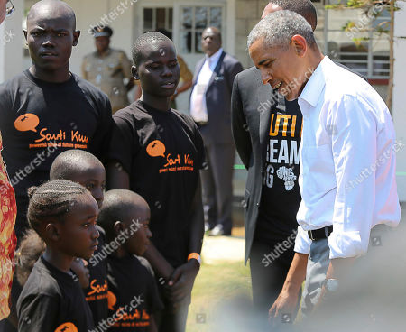 Former US President Barack Obama, right, talk to children in Kogelo, Kisumu, Kenya, . Obama is in Kenya to launch a sports and training center founded by his half-sister, Auma Obama