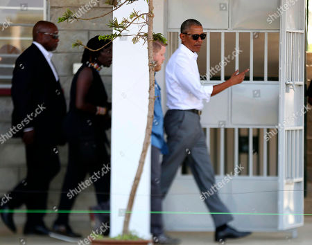 Former US President Barack Obama, right, and his half sister Auma Obama, second left, walk around the training centre at Kogelo, Kenya, . Former U.S. President Barack Obama Monday praised Kenya's president and opposition leader for working together but said this East African country must do more to end corruption. Obama, on his first visit to Africa since stepping down as president, commended President Uhuru Kenyatta and opposition leader Raila Odinga for cooperating following last year's disputed presidential election which were marked by violence