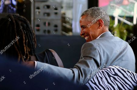 Former US President Barack Obama speaks with his half sister Auma Obama, in Kogelo, Kenya, . Former U.S. President Barack Obama Monday praised Kenya's president and opposition leader for working together but said this East African country must do more to end corruption. Obama, on his first visit to Africa since stepping down as president, commended President Uhuru Kenyatta and opposition leader Raila Odinga for cooperating following last year's disputed presidential election which were marked by violence