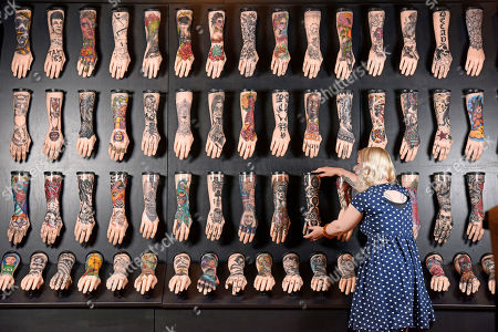 Curator of exhibitions for the National Museum, Alice Roberts-Pratt, straightens one of the hands in the 100 hands display.