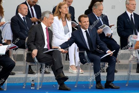 French President Emmanuel Macron (C) stands with Singapore's Prime Minister Lee Hsien Loong (L) his wife Brigitte Trogneux (C/R), French Labour Minister Muriel Penicaud, French Justice Minister Nicole Belloubet, French Junior Minister for the Digital Sector Mounir Mahjoubi, French Junior Minister for Foreign Affairs Jean-Baptiste Lemoyne, French Junior Minister for Economy Delphine Geny-Stephann, French Interior Minister Gerard Collomb, French Minister for the Territorial Cohesion Jacques Mezard and French Prime Minister Edouard Philippe during the annual Bastille Day military parade on the Champs-Elysees avenue