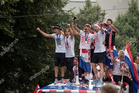 Croatia's national soccer team members, from left, Domagoj Vida, Luka Modric, Sime Vrsaljko, Ante Rebic, Mario Mandzukic and Vedran Corluka, are seen on top of an open bus as they are greeted by fans during a celebration in central Zagreb, Croatia, . In an outburst of national pride and joy, Croatia rolled out a red carpet and staged a euphoric heroes' welcome for the national team on Monday despite its loss to France in the World Cup final