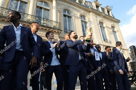 France's defender Adil Rami (C) holds the trophy next to teammates as they pose during a reception at the Elysee Presidential Palace during an official reception in Paris, France, 16 July 2018, after French players won the Russia 2018 World Cup final football match. France celebrated their second World Cup win 20 years after their maiden triumph on July 15, 2018, overcoming a passionate Croatia side 4-2 in one of the most gripping finals in recent history.