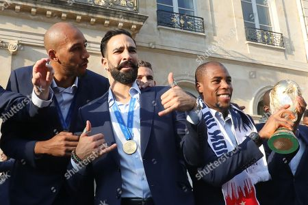 France's defender Djibril Sidibe (R) holds the winner's trophy as France's midfielder Steven N'Zonzi (L) speaks with defender Adil Rami (2nd L) and during an official reception at the Elysee Presidential Palace in Paris, France, 16 July 2018, after French players won the Russia 2018 World Cup final football match. France celebrated their second World Cup win 20 years after their maiden triumph on July 15, 2018, overcoming Croatia 4-2.