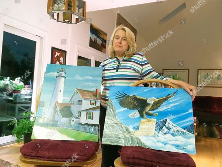 Former Department of Correction counselor Patricia May displays examples of paintings by Delaware prison inmates that decorate her home in Hockessin, Del., . May, a state corrections counselor who was taken hostage during a deadly riot at Delaware's maximum-security prison, says prison officials are to blame. On Tuesday, Gov. John Carney and corrections officials will release a final report on efforts to implement 41 recommendations from an independent review team