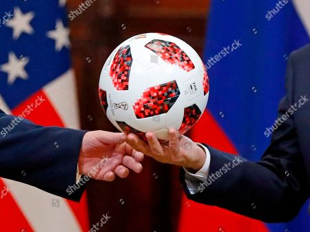 Donald Trump, Vladimir Putin. Russian President Vladimir Putin, right, gives a soccer ball to U.S. President Donald Trump, left, during a press conference after their meeting at the Presidential Palace in Helsinki, Finland
