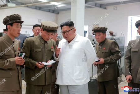 """In this undated photo provided, by the North Korean government, North Korean leader Kim Jong Un, center, speaks during a visit to a machine factory in North Hamgyong Province, North Korea. State media say that Kim has harshly reprimanded local officials over a delayed construction project. Independent journalists were not given access to cover the event depicted in this image distributed by the North Korean government. The content of this image is as provided and cannot be independently verified. Korean language watermark on image as provided by source reads: """"KCNA"""" which is the abbreviation for Korean Central News Agency"""
