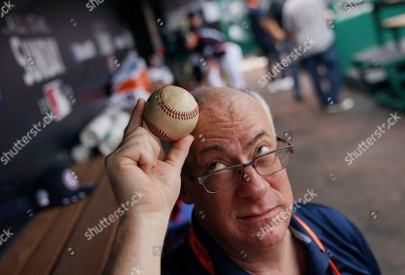 Stock Image of Associated Press baseball writer Ben Walker poses in a dugout with the ball that hit him during the 1969 All-Star game, at Nationals Park, in Washington. That was the last time the Midsummer Classic was in the nation's capital, at RFK Stadium