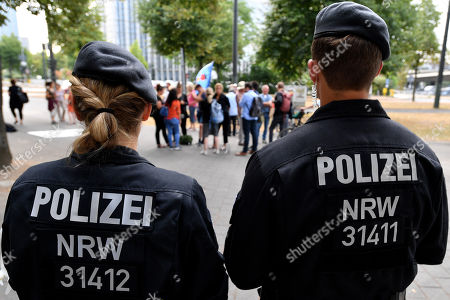 Police officers watch demonstrators gathering to protest against the German asylum policy at the Ministry for Children, Family, Refugees and Integration of North Rhine-Westphalia (NRW) in Duesseldorf, Germany, 17 July 2018. NRW Minister of Refugees Joachim Stamp and Federal Minister of the Interior Horst Seehofer have cancelled a long-planned discussion on asylum policy at short notice. Both politicians are too busy with the controversial deportation of Sami A.. Sami A. is classified as an Islamist threat, lived in Bochum for years and resisted deportation by legal means. On Friday 13 July he was flown out to his home country Tunisia.
