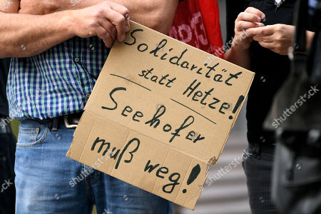 A demonstrator holds a placard reading 'Solidarity instead of agitation - Seehofer must go!' during a protest against the German asylum policy at the Ministry for Children, Family, Refugees and Integration of North Rhine-Westphalia (NRW) in Duesseldorf, Germany, 17 July 2018. NRW Minister of Refugees Joachim Stamp and Federal Minister of the Interior Horst Seehofer have cancelled a long-planned discussion on asylum policy at short notice. Both politicians are too busy with the controversial deportation of Sami A.. Sami A. is classified as an Islamist threat, lived in Bochum for years and resisted deportation by legal means. On Friday 13 July he was flown out to his home country Tunisia.