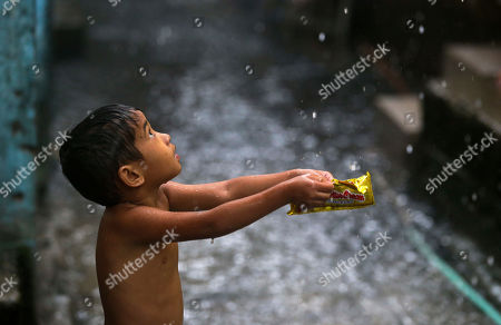 A boy catches water droplets in a flooded village in Navotas, Manila, the Philippines on . Work and schools in several places have been suspended Tuesday as heavy monsoon rains brought on by a tropical storm continue to bring floods in Manila and in other various parts of the country