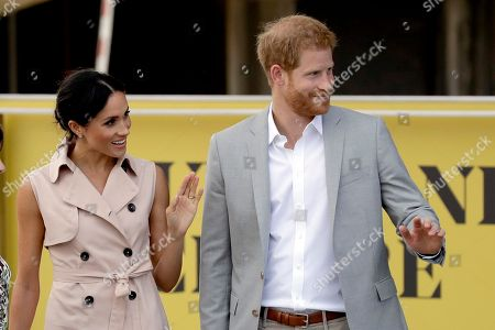 Britain's Prince Harry, right, and his wife Meghan the Duchess of Sussex wave at onlookers as they arrive for their visit to the launch of the Nelson Mandela Centenary Exhibition, marking the 100th anniversary of anti-apartheid leader's birth, at the Queen Elizabeth Hall in London