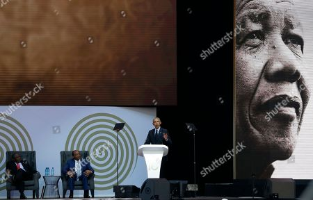 U.S. President Barack Obama, at podium delivers his speech at the 16th Annual Nelson Mandela Lecture at the Wanderers Stadium in Johannesburg, South Africa, . In his highest-profile speech since leaving office, Obama urged people around the world to respect human rights and other values under threat in an address marking the 100th anniversary of anti-apartheid leader Nelson Mandela's birth