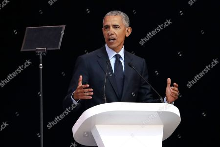 Former U.S. President Barack Obama, left, delivers his speech at the 16th Annual Nelson Mandela Lecture at the Wanderers Stadium in Johannesburg, South Africa, . In his highest-profile speech since leaving office, Obama urged people around the world to respect human rights and other values under threat in an address marking the 100th anniversary of anti-apartheid leader Nelson Mandela's birth