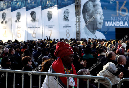 Members of the public sit beneath a banner of former President Nelson Mandela, right, where former U.S. President Barack Obama delivered his speech at the 16th Annual Nelson Mandela Lecture at the Wanderers Stadium in Johannesburg, South Africa, . In his highest-profile speech since leaving office, Obama urged people around the world to respect human rights and other values under threat in an address marking the 100th anniversary of anti-apartheid leader Nelson Mandela's birth