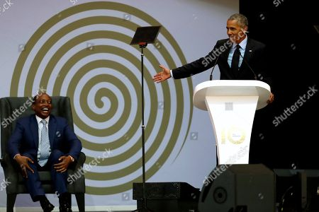 Former U.S. President Barack Obama, right, delivers his speech, as Patrice Motsepe, left, looks on at the 16th Annual Nelson Mandela Lecture at the Wanderers Stadium in Johannesburg, South Africa, . In his highest-profile speech since leaving office, Obama urged people around the world to respect human rights and other values under threat in an address marking the 100th anniversary of anti-apartheid leader Nelson Mandela's birth