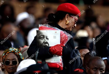 A woman holds a program with a portrait of former President Nelson Mandela, before former U.S. President Barack Obama delivered his speech at the 16th Annual Nelson Mandela Lecture at the Wanderers Stadium in Johannesburg, South Africa, . In his highest-profile speech since leaving office, Obama urged people around the world to respect human rights and other values under threat in an address marking the 100th anniversary of anti-apartheid leader Nelson Mandela's birth