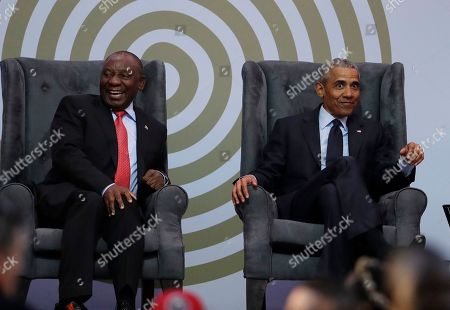 South African President Cyril Ramaphosa, left, and former U.S. President Barack Obama, right, share a light moment at the 16th Annual Nelson Mandela Lecture at the Wanderers Stadium in Johannesburg, South Africa, . In his highest-profile speech since leaving office, Obama urged people around the world to respect human rights and other values under threat in an address marking the 100th anniversary of anti-apartheid leader Nelson Mandela's birth