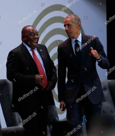 South African President Cyril Ramaphosa, left, and former U.S. President Barack Obama, right, share a ligh moment at the 16th Annual Nelson Mandela Lecture at the Wanderers Stadium in Johannesburg, South Africa, . In his highest-profile speech since leaving office, Obama urged people around the world to respect human rights and other values under threat in an address marking the 100th anniversary of anti-apartheid leader Nelson Mandela's birth