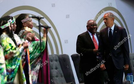 South African President Cyril Ramaphosa, center, and former U.S. President Barack Obama, right, in front of members of the Soweto Gospel Choir share a light moment at the 16th Annual Nelson Mandela Lecture at the Wanderers Stadium in Johannesburg, South Africa, . In his highest-profile speech since leaving office, Obama urged people around the world to respect human rights and other values under threat in an address marking the 100th anniversary of anti-apartheid leader Nelson Mandela's birth