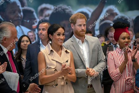 Britain's Prince Harry, center right, and Meghan the Duchess of Sussex attend the launch of the Nelson Mandela Centenary Exhibition, marking the 100th anniversary of anti-apartheid leader's birth, at the Queen Elizabeth Hall in London