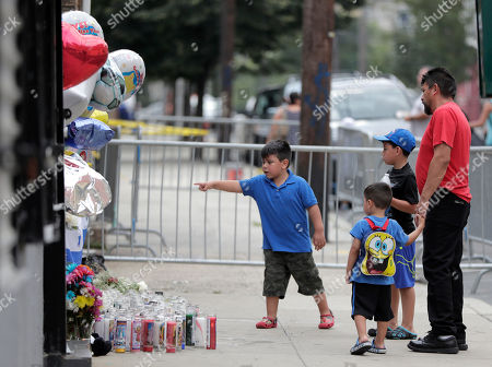 Matthew Romero, 5, left, points at a makeshift memorial while standing with his brothers Derrick, 3, center left, and Andy, 6, center right and their father, Luis Romero, near the site of a house fire that left five children dead, in Union City, N.J. The Hudson County prosecutor's office announced Tuesday that 4-year-old Shamira Lopez has died. Officials have previously said that Friday morning's fire at the three-story home also killed three boys _ 2-year-old Jason Gonzalez, 7-year-old Christian Josue Mendez and 13-year-old Jose Felipe Tejada _ and a 5-year-old girl, Mayli Wood. A woman and a man injured in the fire are in stable condition