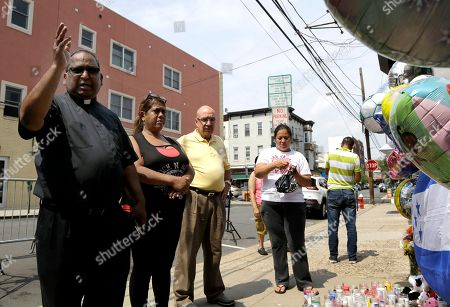 Father Nathan Aro, left, of Saints Joseph and Michael Church, gives his blessing after praying in front of a makeshift memorial at the site of a house fire that left five children dead, in Union City, N.J. The Hudson County prosecutor's office announced Tuesday that 4-year-old Shamira Lopez has died. Officials have previously said that Friday morning's fire at the three-story home also killed three boys; 2-year-old Jason Gonzalez, 7-year-old Christian Josue Mendez and 13-year-old Jose Felipe Tejada, and a 5-year-old girl, Mayli Wood. A woman and a man injured in the fire are in stable condition