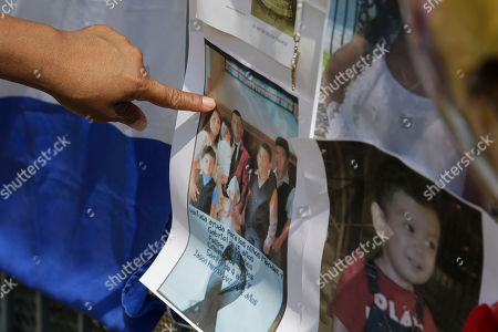 Nidia Castro points at a family portrait showing some of the victims of a house fire at a makeshift memorial near the site of the fire that left five children dead, in Union City, N.J. The Hudson County prosecutor's office announced Tuesday that 4-year-old Shamira Lopez has died. Officials have previously said that Friday morning's fire at the three-story home also killed three boys, 2-year-old Jason Gonzalez, 7-year-old Christian Josue Mendez and 13-year-old Jose Felipe Tejada, and a 5-year-old girl, Mayli Wood. A woman and a man injured in the fire are in stable condition