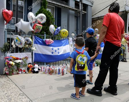 Derrick Romero, 3, left, holds the hand of his father, Luis Romero, while visiting a makeshift memorial near the site of a house fire that left five children dead, in Union City, N.J. The Hudson County prosecutor's office announced Tuesday that 4-year-old Shamira Lopez has died. Officials have previously said that Friday morning's fire at the three-story home also killed three boys, 2-year-old Jason Gonzalez, 7-year-old Christian Josue Mendez and 13-year-old Jose Felipe Tejada, and a 5-year-old girl, Mayli Wood. A woman and a man injured in the fire are in stable condition