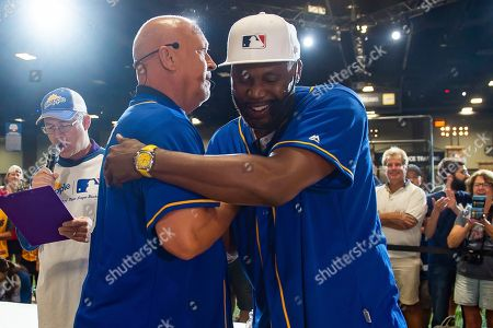"""Cal Ripken Jr. congratulates Cliff Floyd after Snapple's first-ever All-Star Bottle Flip Challenge at MLB FanFest for winning the title of """"Flip for Flavor"""" champion by accurately flipping Snapple bottles onto fruit bases, in Washington"""