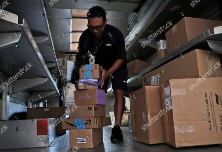 A FedEx employee delivers packages in Miami. Amazon Prime Day was launched July 16 and and will be six hours longer than last year's and will launch new products