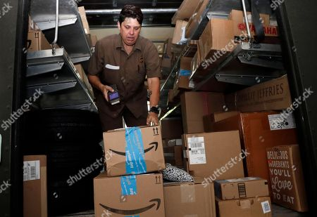 United Parcel Service employee Liz Perez scans an Amazon Prime package for delivery in Miami, . Amazon Prime Day was launched July 16. The event is in four new countries this year and will be six hours longer than last year's