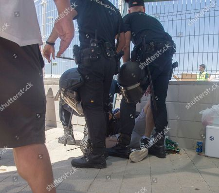 Group of policemen seen holding one of the detainees on the ground during the police charge