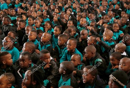 Children attend a special assembly to mark Mandela Day, at Melpark Primary School, in Johannesburg, . South Africans along with former U.S. President Barack Obama are marking the centennial of Nelson Mandela's birth with acts of charity in a country still struggling with deep economic inequality 24 years after the end of white minority rule