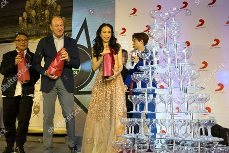 Hong Kong singer-actress Karen Mok, center, and Chief Operating Officer Sony Music Entertainment Kevin Kelleher, second from left, prepare to pour onto a champagne tower to celebrate their new co-created music label during a ceremony in Beijing, China