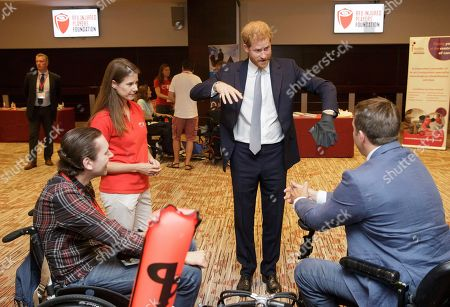 Britain's Prince Harry, Duke of Sussex, with Karen Hood, head of the IPF, tries a diving glove as he meets scuba divers Tom Horay, left, and Tom Hugues, right, who plan to teach diving to Injured Players Foundation (IPF) members, during a visit to the RFU Injured Players Foundation's annual Client Forum at Twickenham Stadium, in London, . The RFU Injured Players Foundation provides information and support to players who sustain catastrophic injury, and uses research and education to help prevent future injuries