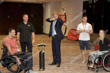Britain's Prince Harry, Duke of Sussex, tries archery as he meets Liam O-Keefe from Bristol, left, with Dani Watts from London, right, during a visit to the RFU Injured Players Foundation (IPF) annual Client Forum at Twickenham Stadium, in London, . The RFU Injured Players Foundation provides information and support to players who sustain catastrophic injury, and uses research and education to help prevent future injuries