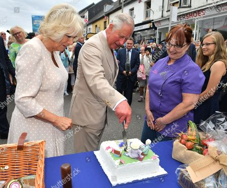 Prince Charles and Camilla Duchess of Cornwall cutting a cake as they visit the 'Gate-to-Plate' food market in Honiton, Devon.