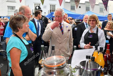 Prince Charles tastes fruit juice from the Bloom Berry Juice Company as he visits the 'Gate-to-Plate' food market in Honiton, Devon.