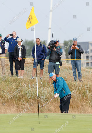 Sandy Lyle (SCO) chips on to the first green after playing the first tee shot of the 147th Open Championship at 06:35