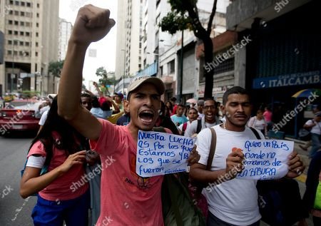 """Demonstrators hold signs that reads in Spanish """"Our fight is for those of us who stayed and those who left,"""" left, and """"I want a country where we don't eat from the garbage"""" as they shout slogans against Venezuela's President Nicolas Maduro in downtown Caracas, Venezuela, . The previous night, former presidential candidate and opposition leader Henrique Capriles called on the country's political forces to reorganize in order to cope with the South American country's hyperinflation, and lack of food and medicine"""