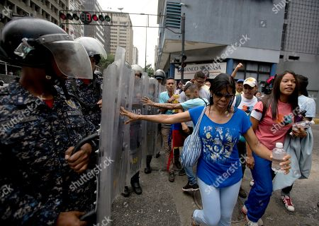 Demonstrators push police's shields as they protest Venezuela's President Nicolas Maduro near the attorney generals office in Caracas, Venezuela, . The previous night, former presidential candidate and opposition leader Henrique Capriles called on the country's political forces to reorganize in order to cope with the South American country's hyperinflation, and lack of food and medicine