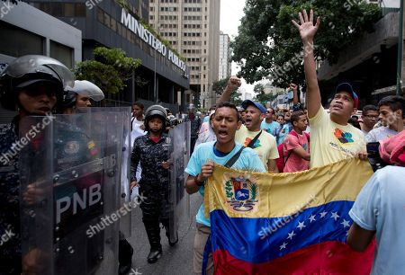 Opposition Leader Leocenis Garcia, right, with members of his party, shout slogans against Venezuela's President Nicolas Maduro outside the attorney generals office where police stand on guard in downtown Caracas, Venezuela, . The previous night, former presidential candidate and opposition leader Henrique Capriles called on the country's political forces to reorganize in order to cope with the South American country's hyperinflation, and lack of food and medicine