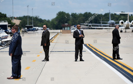 Secret Service agents stand still before U.S. President Donald Trump and First Lady Melania Trump arrive at Joint Airforce Base Andrews to pay their respects to the family of fallen United States Secret Service Special Agent Nole Edward Remagen who suffered a stroke while on duty in Scotland