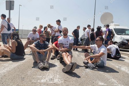 Men are seen sitting in the middle of the street during the protest.