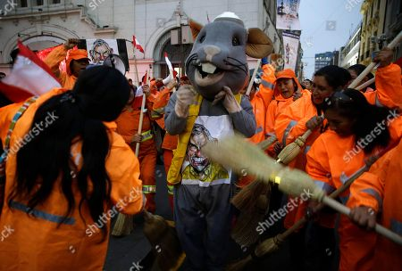 Street sweepers clean a man dressed as a rat representing corruption, during a protest at San Martin plaza, in Lima, Peru, . The latest scandal to embroil this South American nation has ensnared some of the country's highest-ranking judges and political officials and comes just four months after then-President Pedro Pablo Kuczynski stepped down in a separate corruption probe